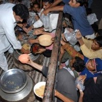Pakistani poor people struggle to get free food at a local shrine in Multan, Pakistan on Thursday, Oct 16, 2008. Pakistan, where the level of poverty is getting high, will observe the International Day for the Eradication of Poverty on October 17. (AP Photo/Khalid Tanveer)