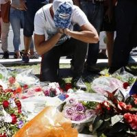 A man reacts near bouquets of flowers in Nice France