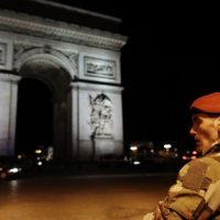 a soldier stand near the arc de triomphe